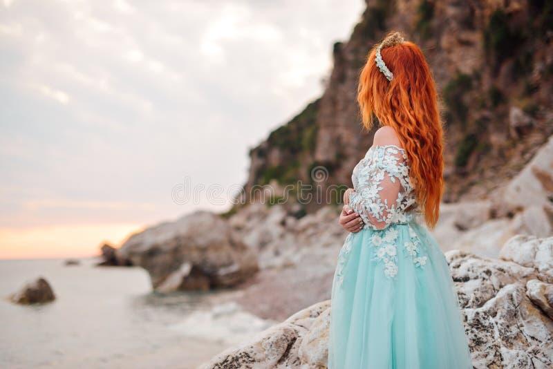 Junge Frau in einem luxuriösen Kleid steht auf dem Ufer des adriatischen Meeres lizenzfreies stockbild