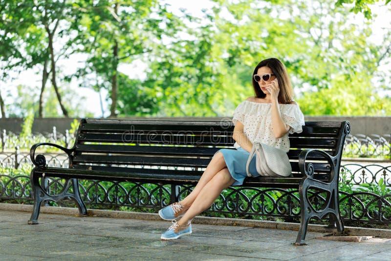 Junge Frau in einem Park in einer weißen Bluse und in einem blauen Rock ist sittin stockbild