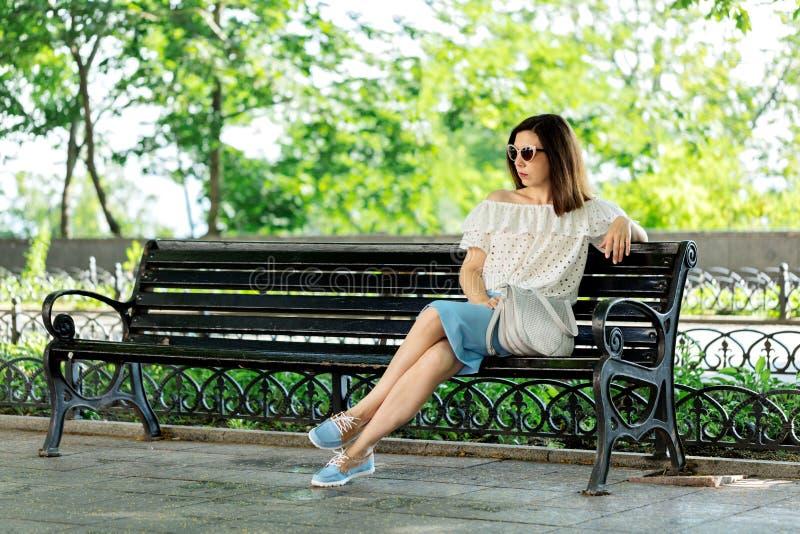 Junge Frau in einem Park in einer weißen Bluse und in einem blauen Rock ist sittin stockbilder