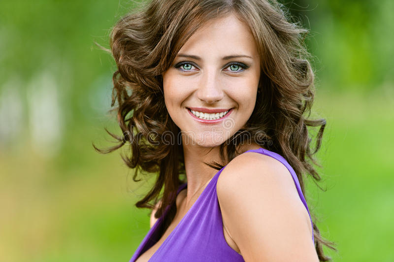 Junge Frau in einem purpurroten Kleid lizenzfreie stockbilder