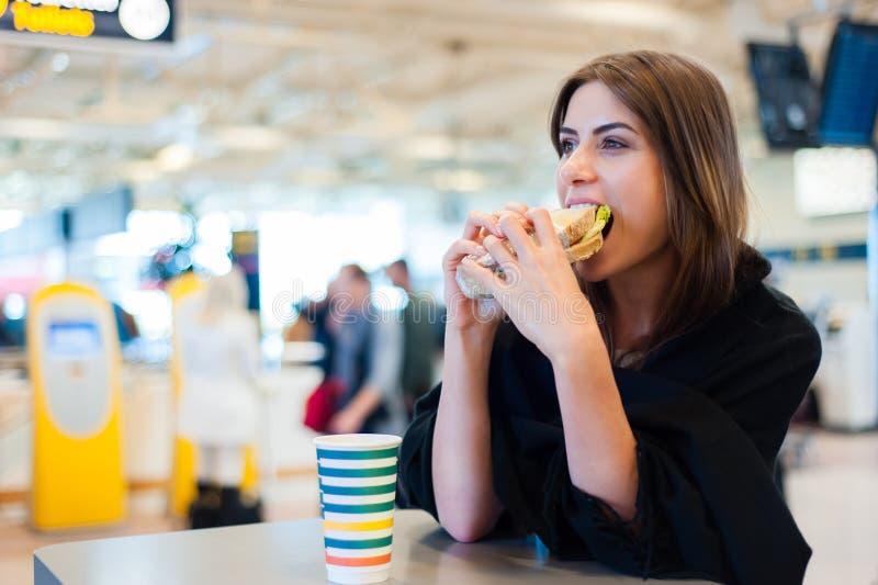 Junge Frau an einem Restaurant im internationalen Flughafen stockfotos