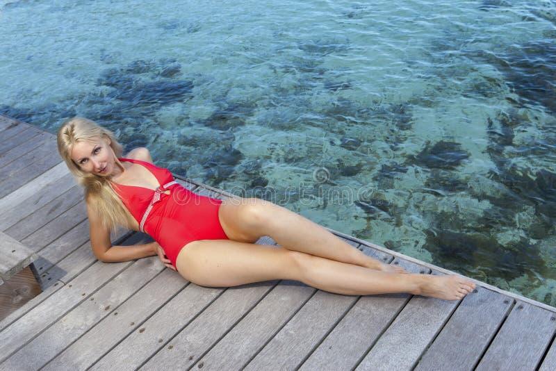 Junge Frau in einem roten Badeanzug auf Seehintergrund stockbild