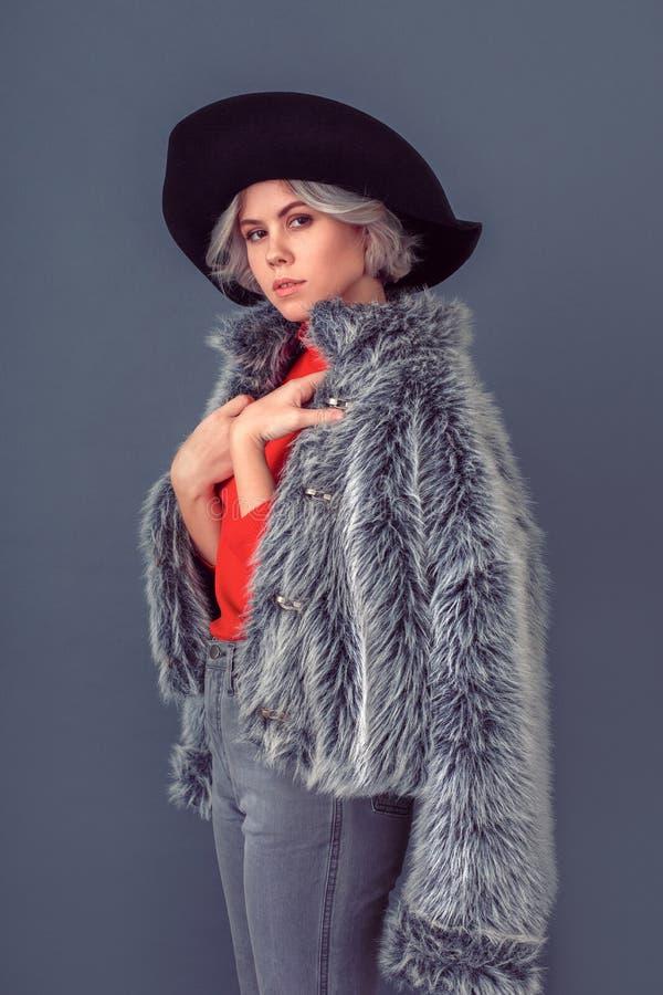 Junge Frau in einem roten Blusen- und Pelzmantel auf der grauen Wandaufstellung stockfotos