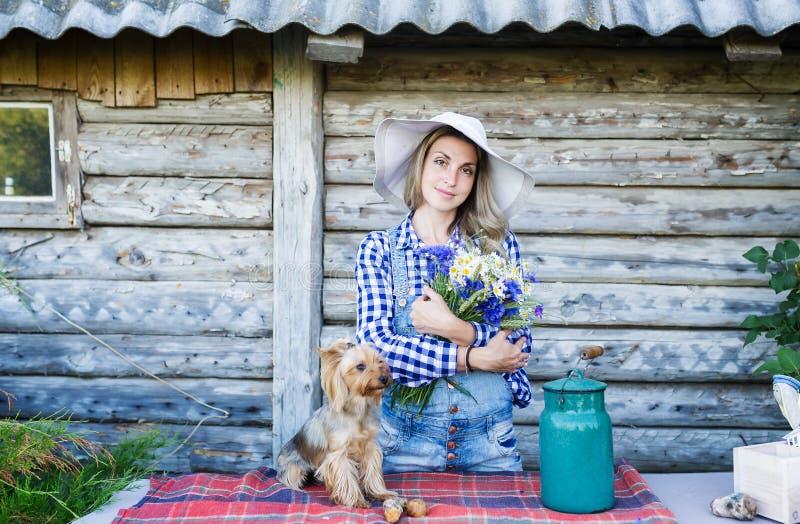 Junge Frau in einem Strohsommerhut und in ihrem kleiner Hundeländlichen Hintergrund lizenzfreies stockbild