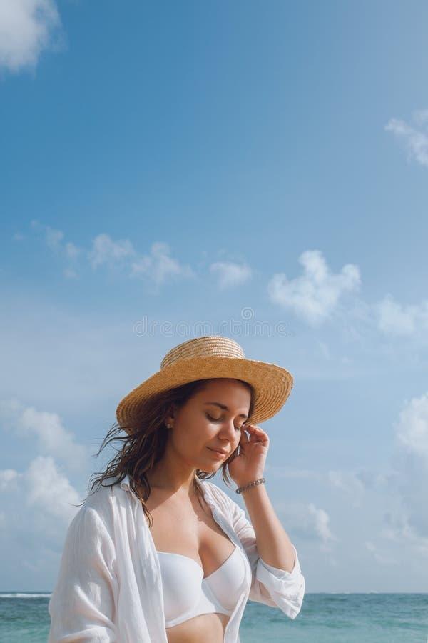Junge Frau in einem weißen Badeanzug und in einem Hut ein Sonnenbad nehmend auf dem Strand lizenzfreie stockfotografie
