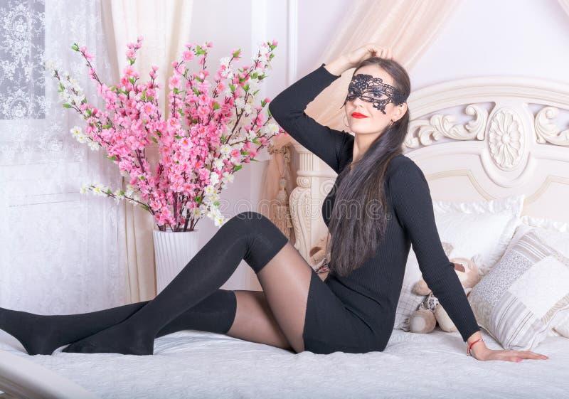 Junge Frau in einer Maske auf dem Bett lizenzfreie stockfotografie