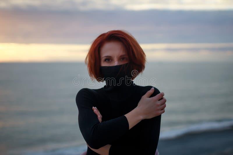 Junge Frau in einer schwarzen Strickjacke mit einem mysteriösen Blick ist gegen den Sonnenuntergang stockbild