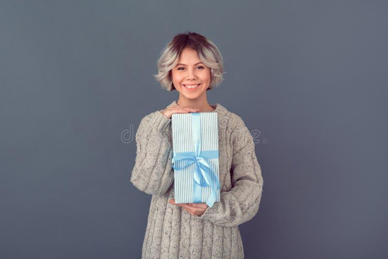 Junge Frau in einer woolen Strickjacke auf grauem Wandwinter-Konzeptgeschenk stockfotografie
