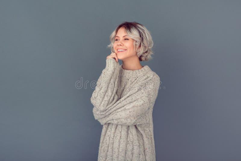 Junge Frau in einer woolen Strickjacke lokalisiert auf dem grauen Wandwinter-Konzeptträumen lizenzfreie stockfotos