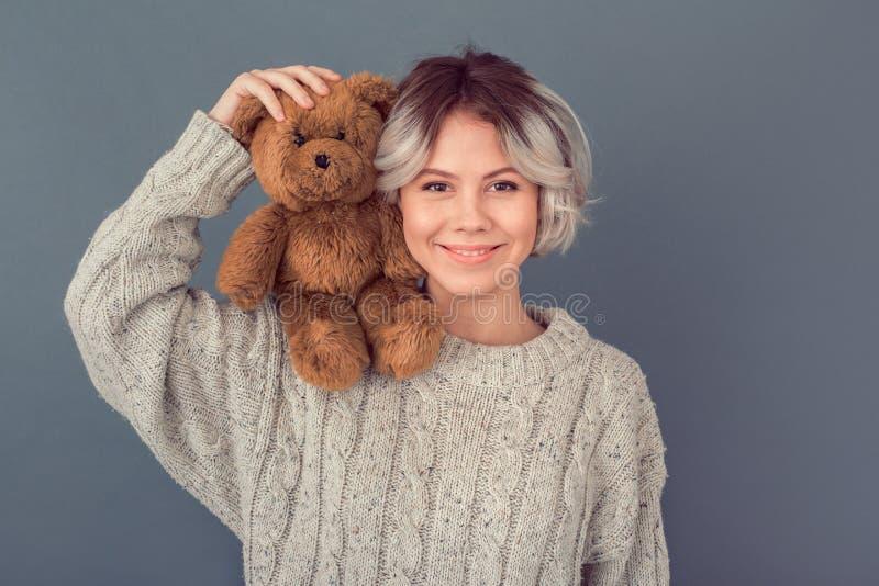 Junge Frau in einer woolen Strickjacke lokalisiert auf dem grauen Wandwinterkonzept, das Teddybären hält lizenzfreies stockfoto
