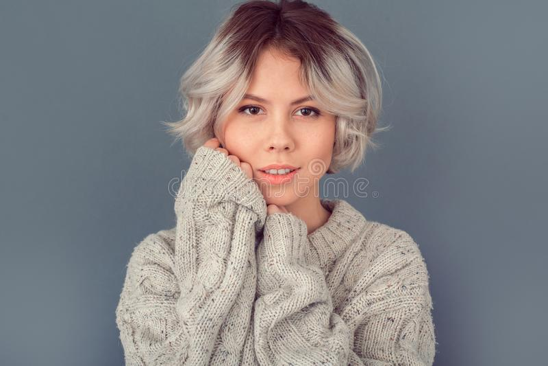 Junge Frau in einer woolen Strickjacke lokalisiert auf grauer Wandwinter-Konzeptmode lizenzfreies stockbild