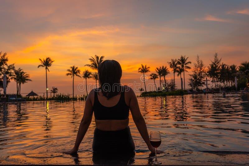 Junge Frau entspannen sich auf dem Poolerholungsort bei Sonnenuntergang stockfotografie