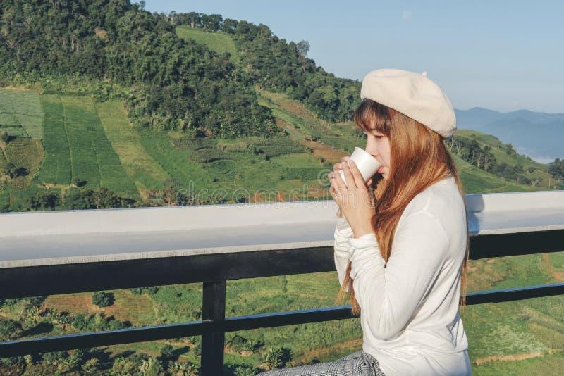 Junge Frau Entspannungsund trinkender Kaffee auf Gebirgscafé lizenzfreies stockfoto