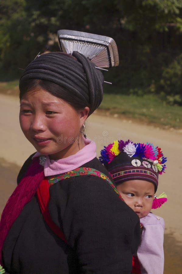 Junge Frau ethnisches schwarzes Dao mit ihrem Schätzchen lizenzfreie stockfotos