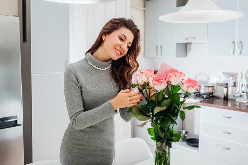 Junge Frau fand Blumenstrauß von Rosen mit Karte auf Küche Glückliche Mädchenleseanmerkung in den Blumen Rote Rose stockfotos