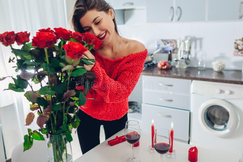 Junge Frau fand rote Rosen mit Kerze, Wein und Geschenkbox auf Küche Riechende Blumen des glücklichen Mädchens Frauen `s Tag stockfotografie