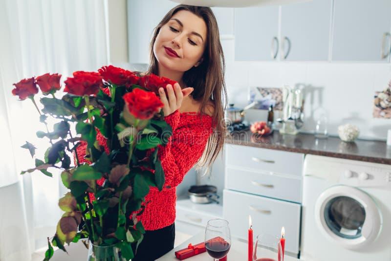Junge Frau fand rote Rosen mit Kerze, Wein und Geschenkbox auf Küche Riechende Blumen des glücklichen Mädchens Rote Rose stockfotografie