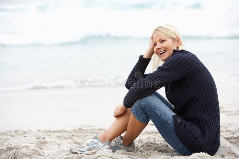 Junge Frau am Feiertag, der auf Winter-Strand sitzt stockbilder