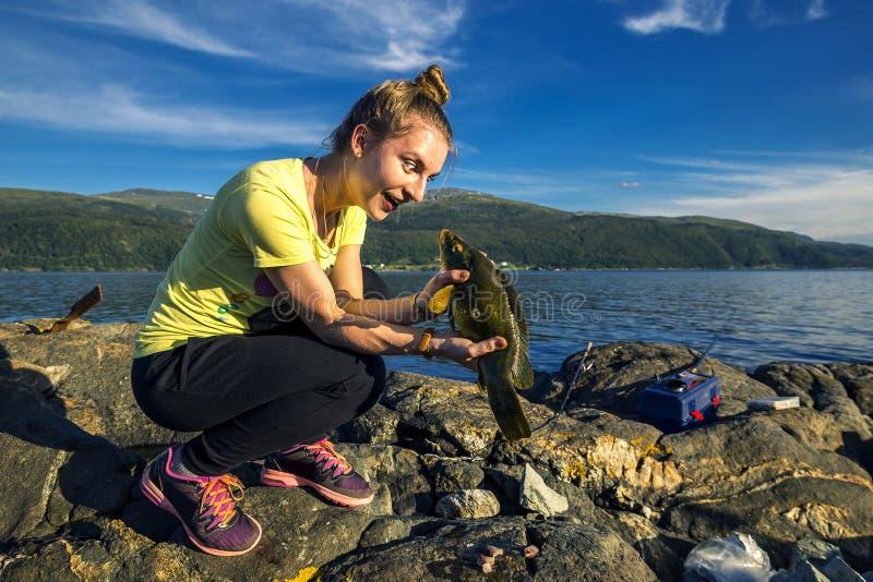 Junge Frau fischt in Norwegen lizenzfreies stockbild