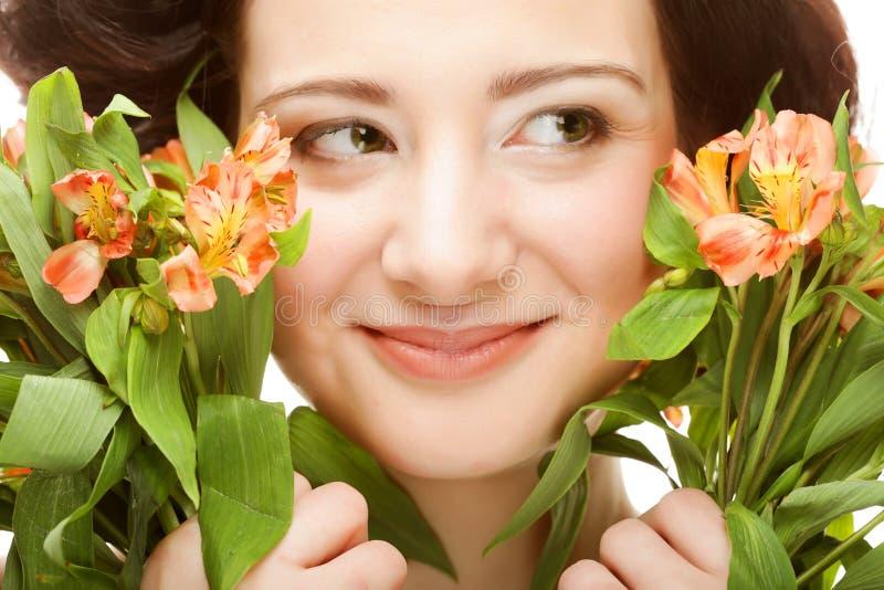 Junge Frau fith helle rosa-gelbe Blumen schließen oben lizenzfreie stockfotografie