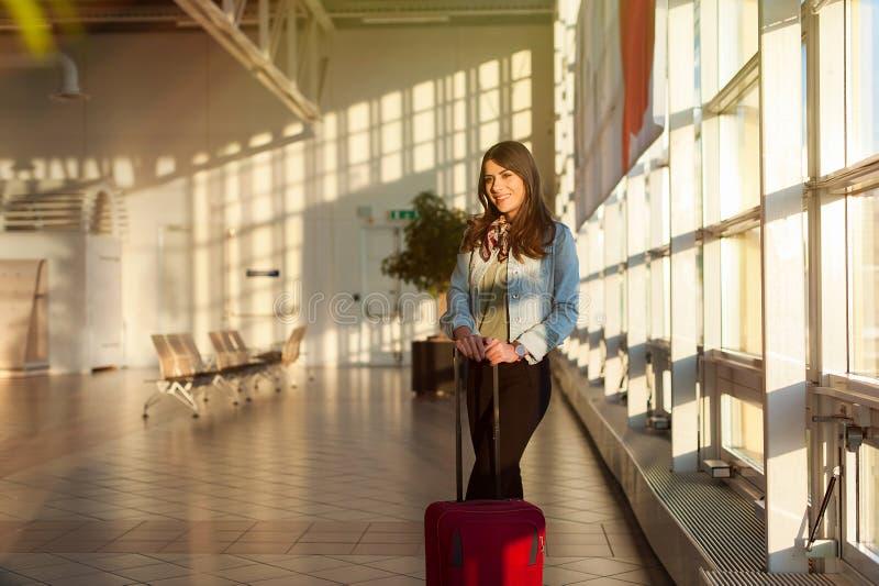 Junge Frau am Flughafenabfertigungsgebäudewarteraum mit Rollkoffer stockfoto