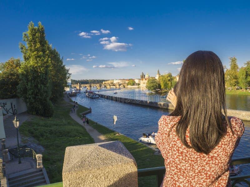 Junge Frau, Foto mit ihrem Handy von der Legions-Brücke mit Ansicht über Kampa-Insel machend, die Moldau-Fluss, Prag Schloss, alt stockbild