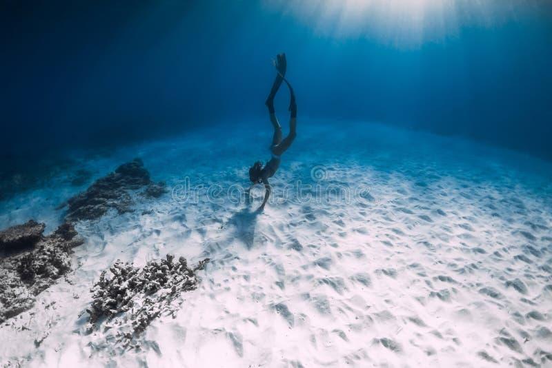 Junge Frau freediver gleitet über sandigem Meeresgrund Freediving im blauen Meer stockfoto