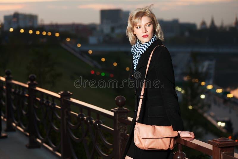 Junge Frau gegen eine Nachtstadt lizenzfreies stockbild