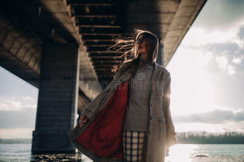 Junge Frau geht auf Flussbank unter Brücke bei Sonnenuntergang lizenzfreie stockfotografie