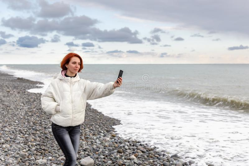 Junge Frau geht durch Küste des Meeres und nimmt ein selfie gegen den Himmel und die Meereswellen stockfotos