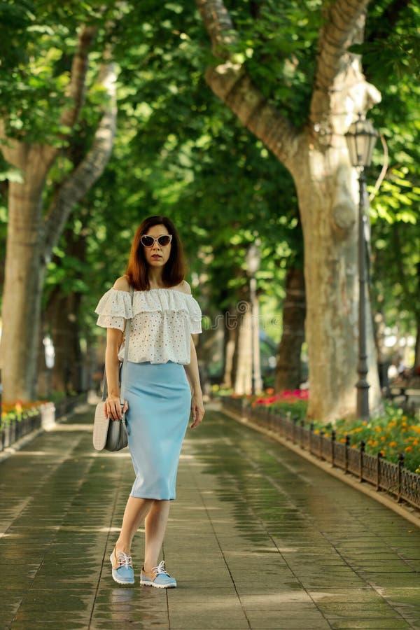 Junge Frau geht in einen Park in einer weißen Bluse und in einem blauen PET stockfotografie