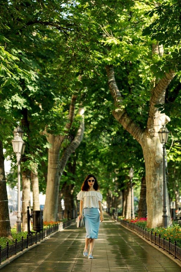 Junge Frau geht in einen Park in einer weißen Bluse und in einem blauen PET lizenzfreies stockbild