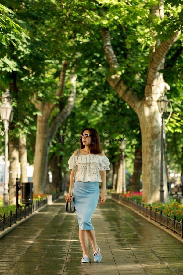 Junge Frau geht in einen Park in einer weißen Bluse und in einem blauen PET lizenzfreie stockbilder