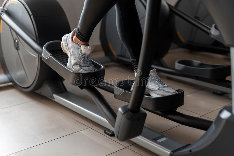 Junge Frau geht in Sportkleidung auf dem Steppersimulator in der Turnhalle Mädchen tut Herz Übungsübungen Gesunder Lebensstil lizenzfreies stockfoto