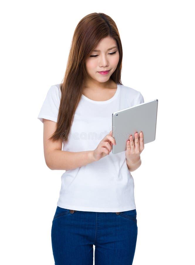 Junge Frau gelesen auf digitaler Tablette lizenzfreie stockbilder