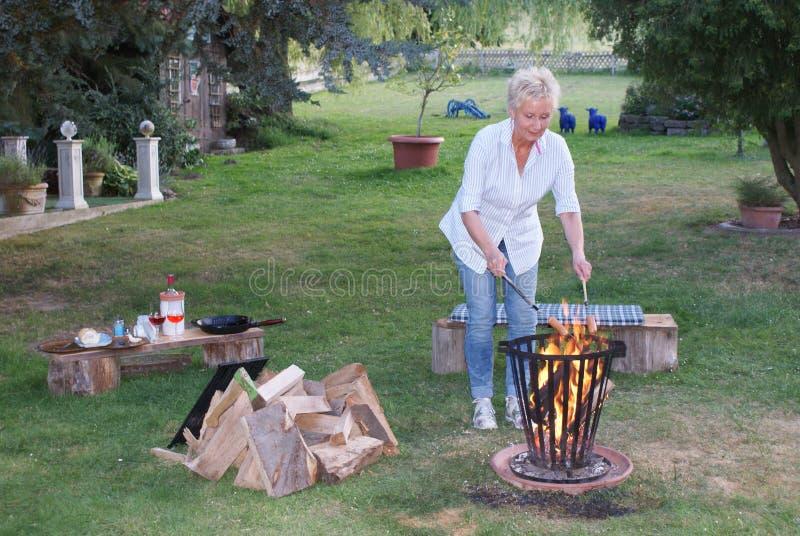 Junge Frau genießt den romantischen Abend durch das Lagerfeuer und grillt Würste stockfotos