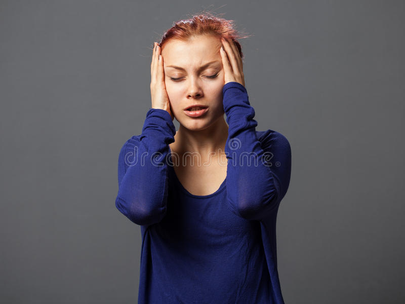 Junge Frau gequält durch Kopfschmerzen stockfoto
