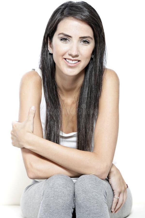 Junge Frau gesessen auf weißem Sofa lizenzfreie stockfotografie