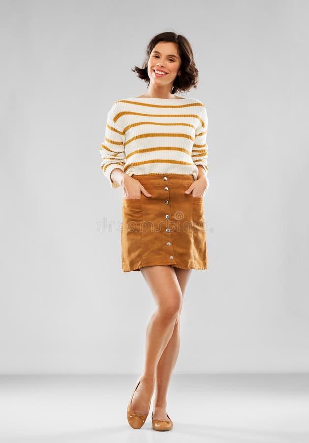 Junge Frau in gestreiftem Pullover, in Rock und in Schuhen stockbild