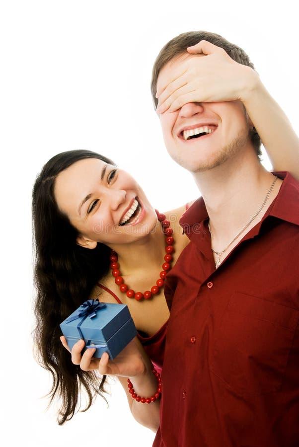Junge Frau gibt ihrem Ehemann ein Geschenk lizenzfreie stockbilder