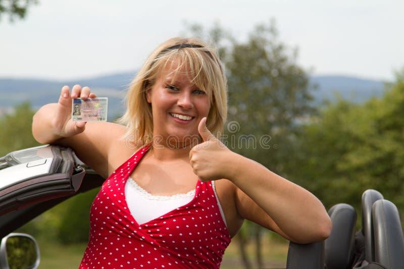 Junge Frau glücklich über ihren neuen Führerschein lizenzfreie stockfotografie