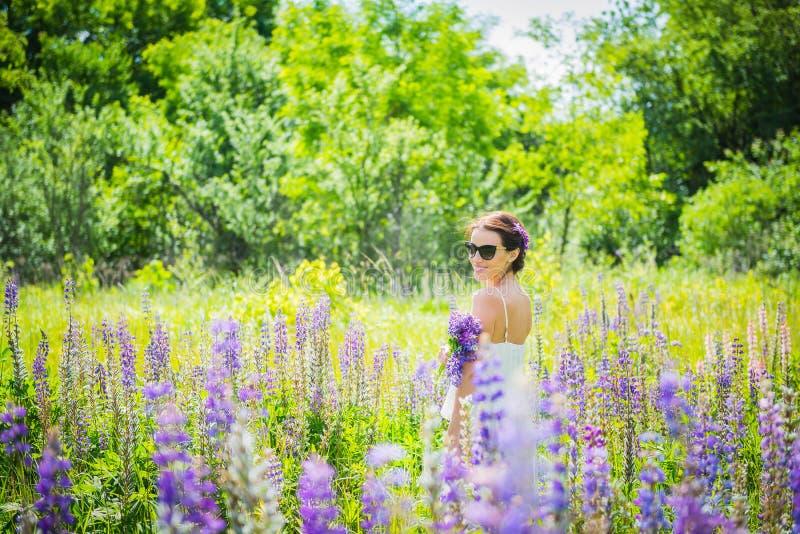 Junge Frau, glücklich, Stellung unter dem Feld von violetten Lupines, lächelnd, purpurrote Blumen Blauer Himmel auf dem Hintergru lizenzfreie stockfotos