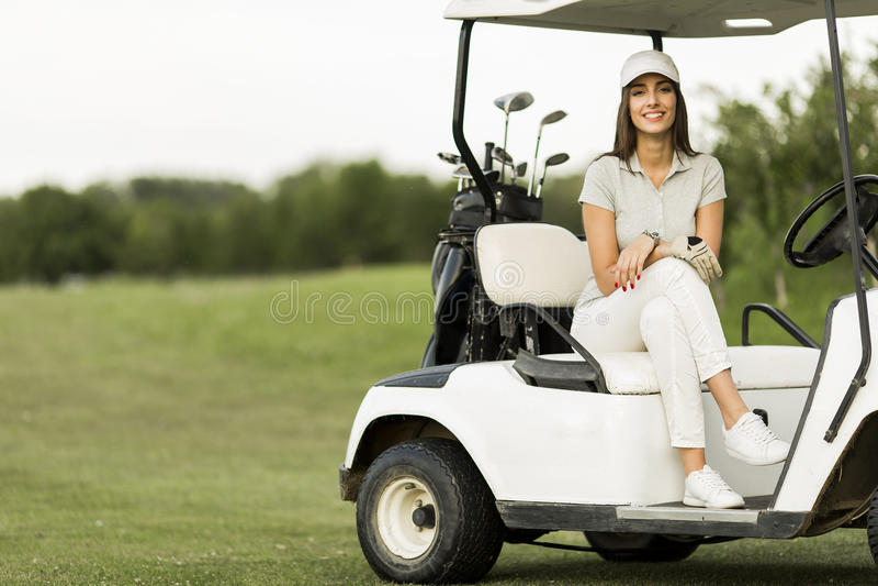Junge Frau am Golfmobil lizenzfreie stockbilder