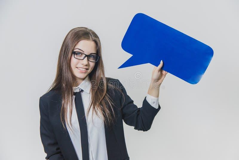 Junge Frau hält eine blaue Spracheblase nahe, das, mit einer Hand, rechteckig ist, auf lizenzfreie stockfotos