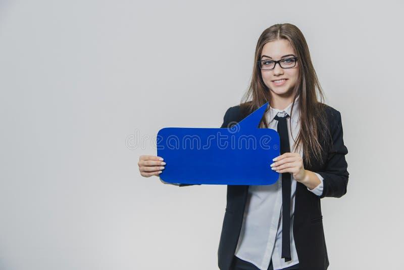 Junge Frau hält eine blaue Spracheblase vor, das, mit einer Hand rechteckig ist, stockfoto