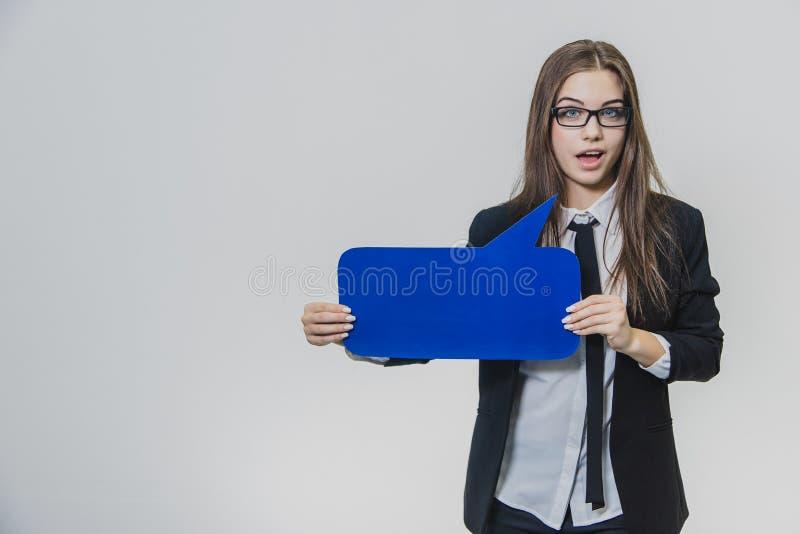 Junge Frau hält eine blaue Spracheblase vor, das rechteckig ist, auf dem Weiß lizenzfreie stockfotografie