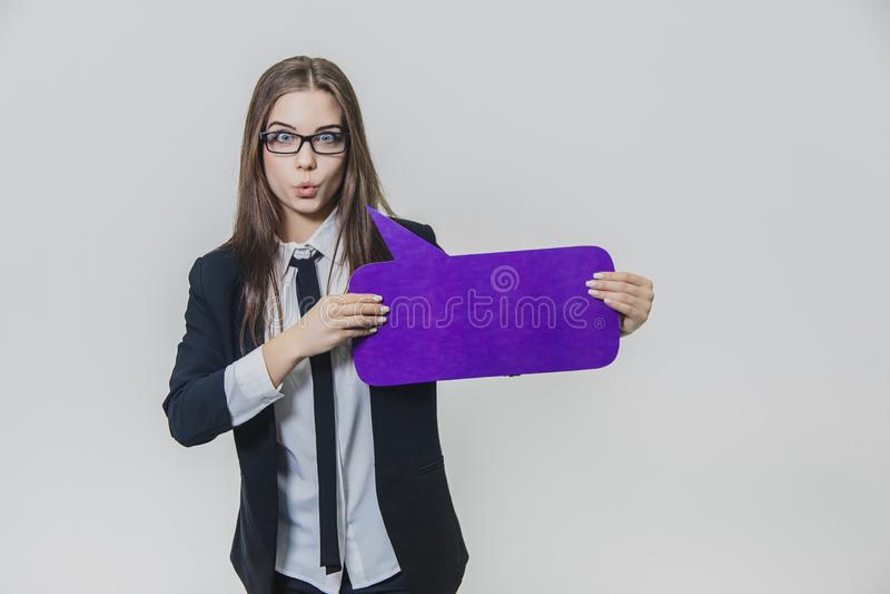 Junge Frau hält eine violette Spracheblase nah an, das rechteckig ist, auf dem Weiß lizenzfreie stockfotografie