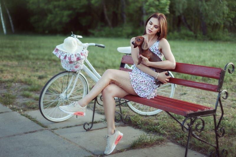 Junge Frau hält einen Hundedachshund lizenzfreie stockbilder