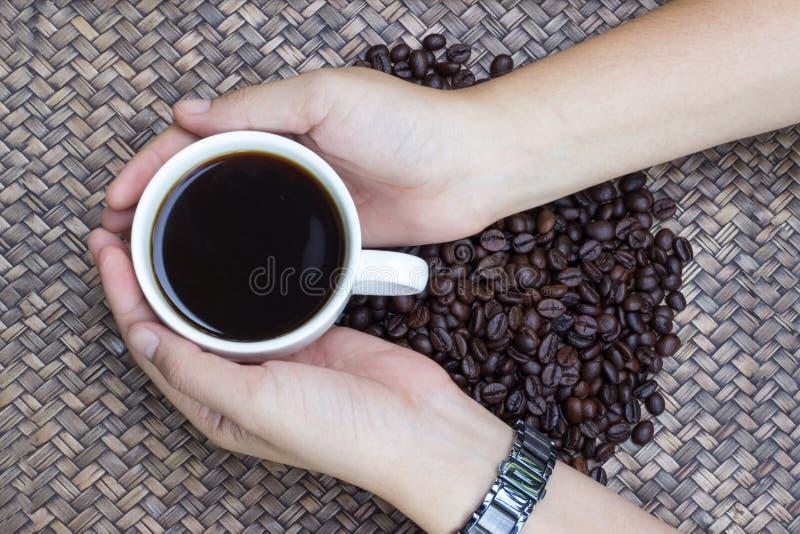Junge Frau hält einen Tasse Kaffee, Kaffeebohnen mit weißer Kaffeetasse stockbilder