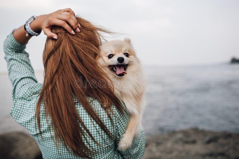 Junge Frau hält Hund draußen stockbild